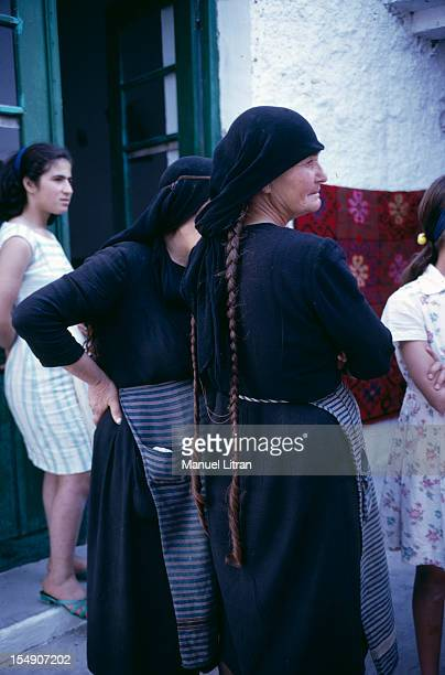 Cretan old women in traditional dress dressed in black wearing a striped apron a black scarf tied over her head leaving appear two long braids