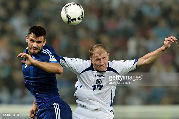 Greece's Alexandros Tziolis fights for thei ball with Bosnia Herzegovina's Senijad Ibricic during their 2014 World Cup qualification football game in...