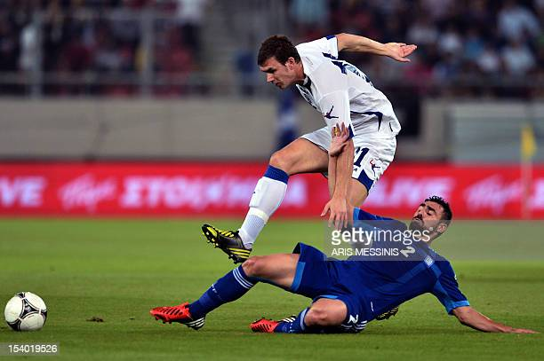 Greece's defender Giannis Maniatis fights for the ball with BosniaHerzegovina's forward Edin Dzeko during their 2014 World Cup qualifier football...