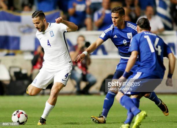 Greece's defender Kostas Manolas attempts to clear the ball as he is marked by Cyprus' forward Pieros Sotiriou and midfielder Vincent Laban during...
