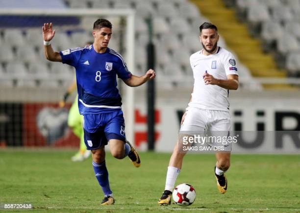 Greece's defender Kostas Manolas attempts to clear the ball as he is marked by Cyprus' forward Pieros Sotiriou during their World Cup 2018 qualifying...