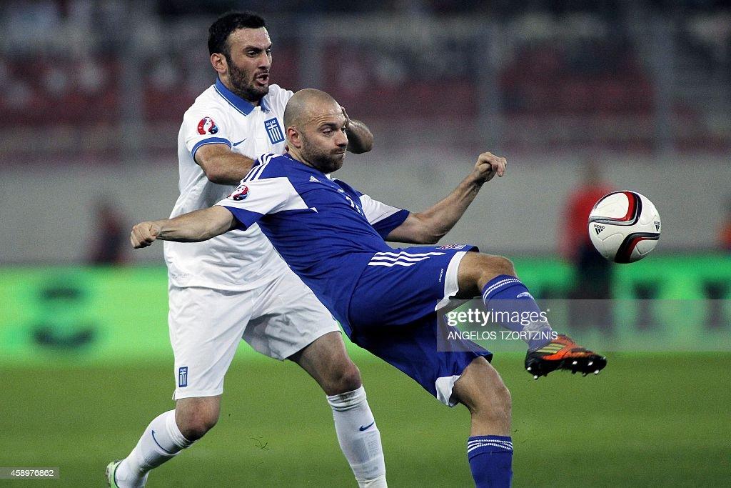 Greece's defender Vasilis Torosidis vies for the ball with Faroe Island's forward Christian Holst during the UEFA Euro 2016 group F qualifying...