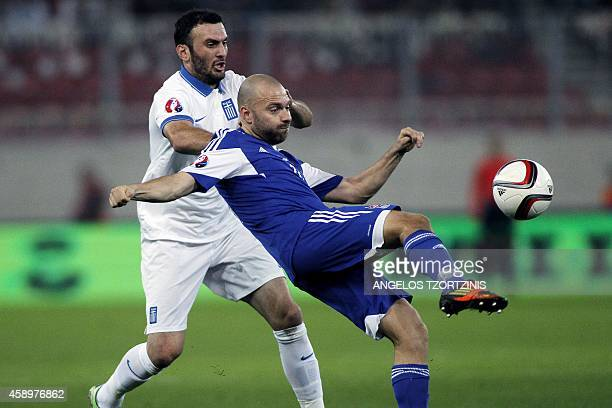 Greece's defender Vasilis Torosidis vies for the ball with Faroe Island's forward Christian Holst during the UEFA Euro 2016 group F qualifying...