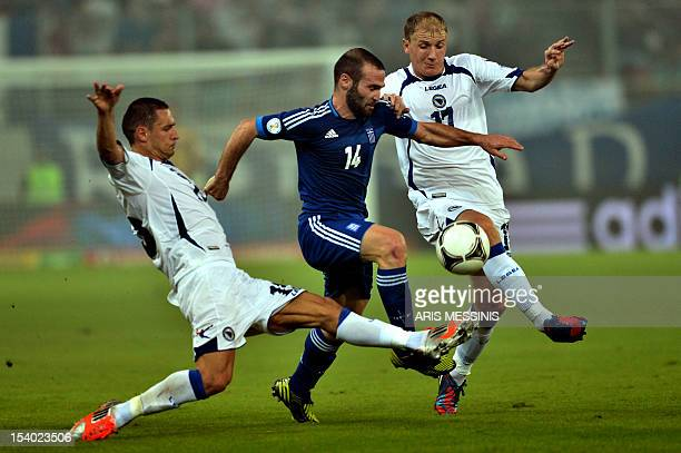 Greece's Dimitris Salpigidis fights for thei ball with Bosnia Herzegovina's Senijad Ibricic and Mensur Mujdza during their 2014 World Cup...