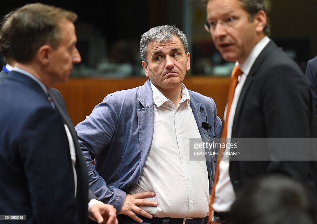 Greece's Finance Minister Euclid Tsakalotos (C) and Eurogroup President and Dutch Finance Minister Jeroen Dijsselbloem (R) attend an Economic and Financial (ECOFIN) Affairs Council meeting at the European Council, in Brussels, on May 25, 2016. / AFP / EMMANUEL