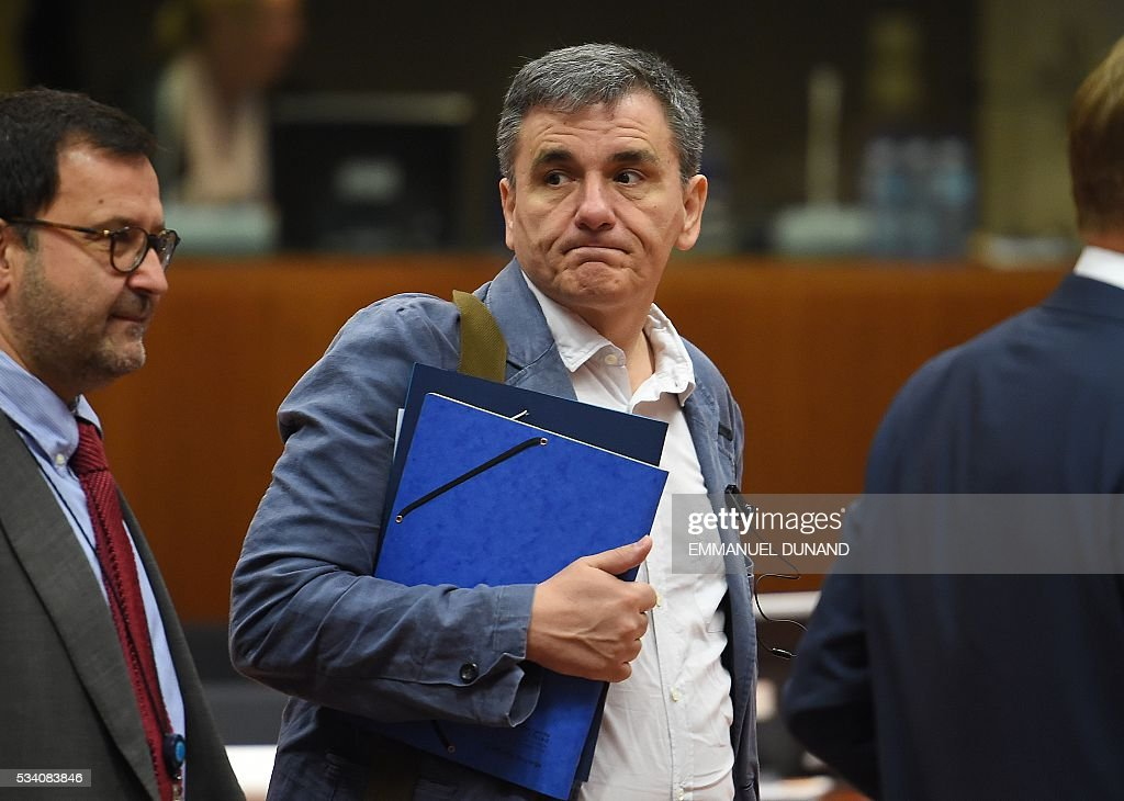 Greece's Finance Minister Euclid Tsakalotos (C) attends an Economic and Financial (ECOFIN) Affairs Council meeting at the European Council, in Brussels, on May 25, 2016. / AFP / EMMANUEL