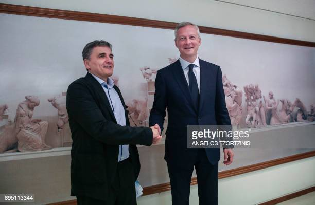 Greece's Finance Minister Euclid Tsakalotos shakes hands with France's Finance Minister Bruno Le Maire during a meeting at the Ministry of Finance in...
