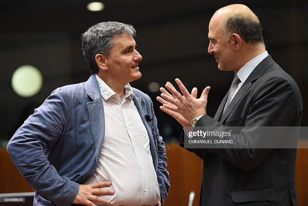 Greece's Finance Minister Euclid Tsakalotos (L) speaks with European Commissioner for Economic and Financial Affairs, Taxation and Customs Pierre Moscovici during an Economic and Financial (ECOFIN) Affairs Council meeting at the European Council, in Brussels, on May 25, 2016. / AFP / EMMANUEL