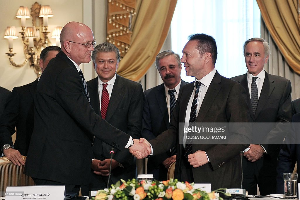 Greece's Finance Minister Yannis Stournaras, (R) shakes hands with Trans Adriatic Pipeline's Managing Director Kjetil Tungland (L) after the signing of an host government agreement in Athens, on June 26, 2013.The consortium developing an immense new Azeri gas field, part of European efforts to reduce dependence on Russia, rejected Wednesday the proposed Nabucco pipeline in favour of a shorter, cheaper route through Greece to Italy. According to an announcement by Austrian company OMV which backs the Nabucco project, the Shah Deniz II consortium, has opted for the rival Trans-Adriatic Pipeline (TAP). AFP PHOTO/ LOUISA GOULIAMAKI