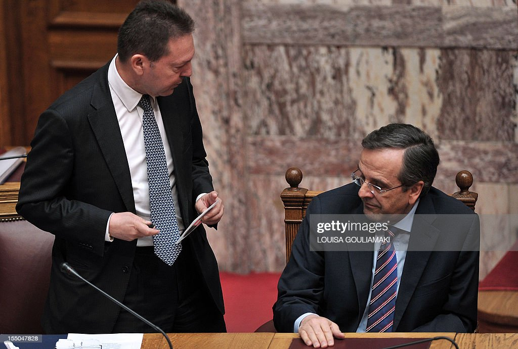 Greece's Finance Minister Yiannis Stournaras (L) holds a disc containing the new draft state budget for 2013 as he talks to Greece's Prime minister Antonis Samaras during a presentation of a draft budget to parliament outlining new austerity measures needed to unlock fresh rescue loans on October 31, 2012, in Athens. Greece revised downwards its recovery forecasts in a 2013 budget that predicted an economic contraction of 4.5 percent of output and a public deficit of 5.2 percent.