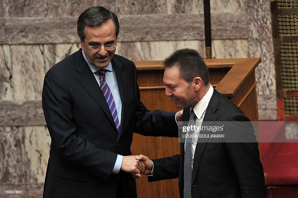 Greece's Finance Minister Yiannis Stournaras (R) shakes hands with Greece's Prime minister Antonis Samaras during a presentation of a draft budget to parliament outlining new austerity measures needed to unlock fresh rescue loans on October 31, 2012 in Athens. Greece revised downwards its recovery forecasts in a 2013 budget that predicted an economic contraction of 4.5 percent of output and a public deficit of 5.2 percent. AFP PHOTO / LOUISA GOULIAMAKI/ GREECE OUT