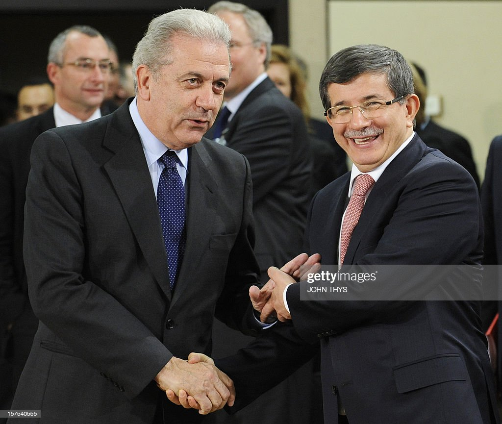 Greece's Foreign Minister Dimitrios Avramopoulos shakes hands with Turkey's Foreign Minister Ahmet Davutoglu (R) during a meeting of foreign affairs ministers from the 28 North Atlantic Treaty Organization (NATO) member-countries to discuss Syria and Turkey's request for Patriot missiles to be deployed protectively on the Turkish-Syrian border at the NATO Headquarters in Brussels, on December 4, 2012. AFP PHOTO / JOHN THYS