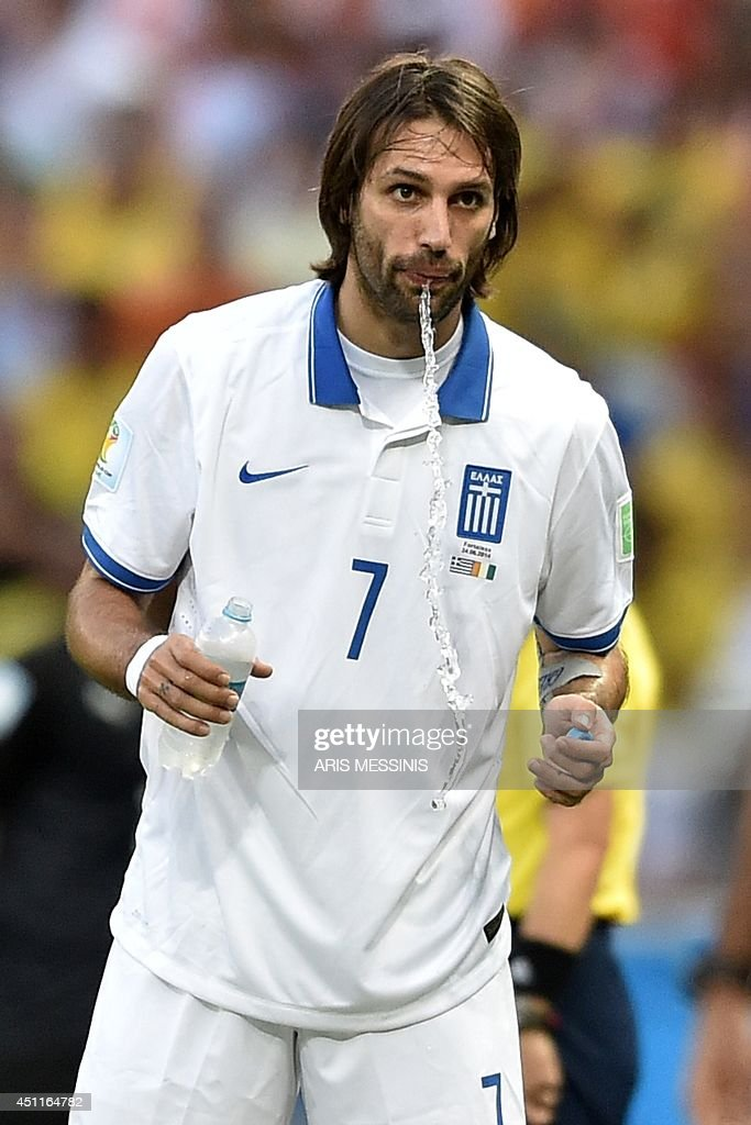 Greece's forward <a gi-track='captionPersonalityLinkClicked' href=/galleries/search?phrase=Georgios+Samaras&family=editorial&specificpeople=616608 ng-click='$event.stopPropagation()'>Georgios Samaras</a> spits water during a Group C football match between Greece and Ivory Coast at the Castelao Stadium in Fortaleza during the 2014 FIFA World Cup on June 24, 2014. AFP PHOTO / ARIS MESSINIS