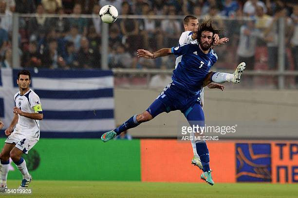 Greece's forward Giorgos Samaras fights for the ball with BosniaHerzegovina's defender Ognjen Vranjes during their 2014 World Cup qualifier football...