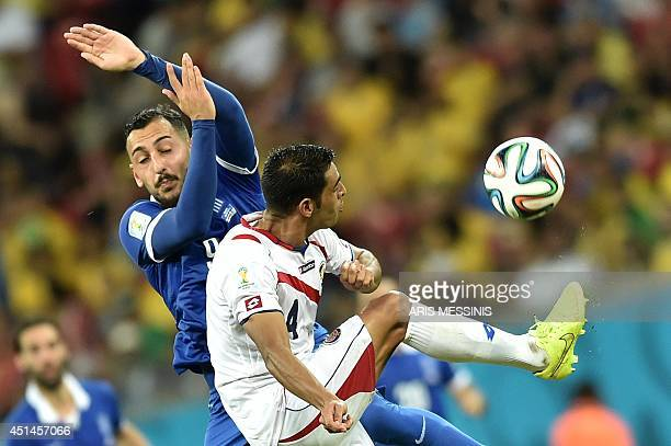 Greece's forward Konstantinos Mitroglou vies with Costa Rica's defender Michael Umana during a Round of 16 football match between Costa Rica and...