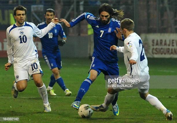 Greece's Georgios Samaras vies zith Bosnia and Herzegovina's Avdija Vrsajevic and Zvjezdan Misimovic during the World Cup 2014 qualifying football...