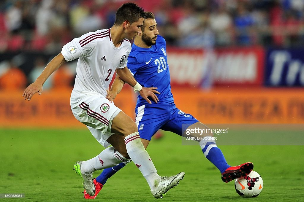 Greece's Giannis Fetfatzidis (R) fights for the ball with Latvia's Vitalijs Maksimenko on September 10, 2013 during a 2014 World Cup qualifying football match in Athens. AFP PHOTO / ARIS Messinis