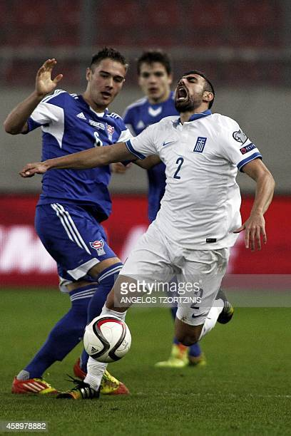 Greece's Giannis Maniatis vies with Faroe Island's Hallur Hansson during the UEFA Euro 2016 group F qualifying football match between Greece and...