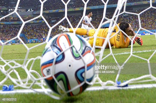 Greece's goalkeeper Orestis Karnezis looks round after Costa Rica's defender Michael Umana scored the winning penalty during a penalty shootout after...