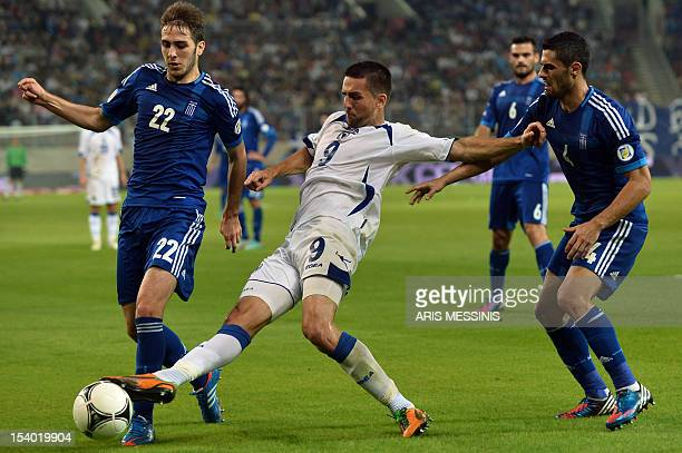 Greece's Kostas Fortounis fights for the ball with Bosnia Herzegovina's Vedad Ibisevic during their 2014 World Cup qualification football game in...