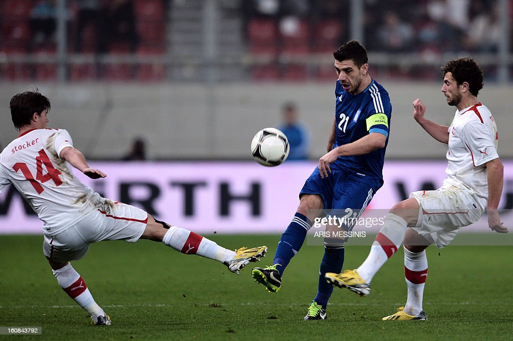 Greece's Kostas Katsouranis (C) fights for the ball on February 6, 2013 with Switzerland's Valentin Stocker (L) during the friendly football match between Switzerland and Greece in Athens.