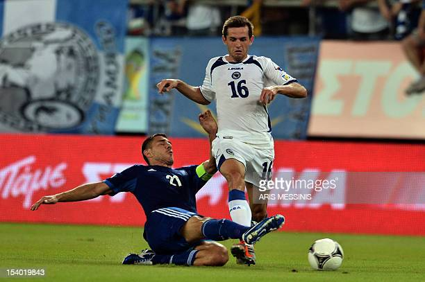 Greece's Kostas Katsouranis fights for the ball with Bosnia Herzegovina's Senad Lulic during their 2014 World Cup qualification football game in...