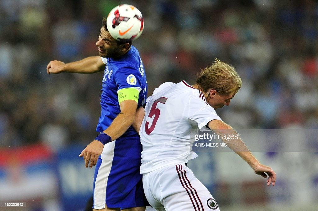 Greece's Kostas Katsouranis (L) fights for the ball with Latvia's Juris Laizans on September 10, 2013 during a 2014 World Cup qualifying football match in Athens. AFP PHOTO / ARIS Messinis