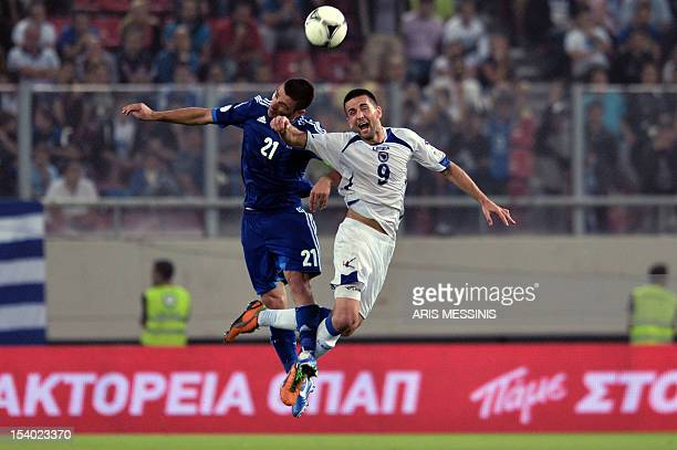 Greece's Kostas Katsouranis fights for the ball with BosniaHerzegovina's Vedad Ibisevic during their FIFA 2014 World Cup qualifier football match...