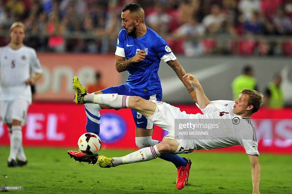 Greece's Kostas Mitroglou (L) fights for the ball with Latvia's Nauris Bulvitis on September 10, 2013 during a 2014 World Cup qualifying football match in Athens. AFP PHOTO / ARIS Messinis