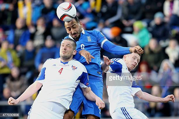 Greece's Kostas Mitroglou vies for the ball with Faroe Island's Atli Gregersen during the UEFA Euro 2016 group F qualifying football match between...