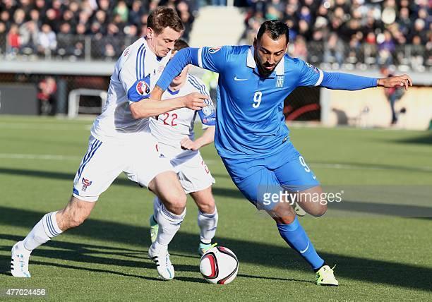 Greece's Kostas Mitroglou vies with Faroe Island's Brandur Olsen during the UEFA Euro 2016 group F qualifying football match between Faroe Island and...