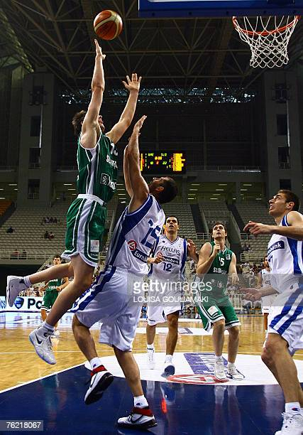 Greece's Michael Kakiouzis tries to block Goran Dragic of Slovenia during their basketball match for the International Basketball tournament...