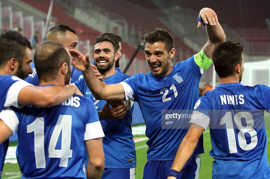 Greece's players celebrate after scoring against Latvia during their 2014 World Cup qualification game in Athens on September 10, 2013. AFP PHOTO / Dimitris Birdachas