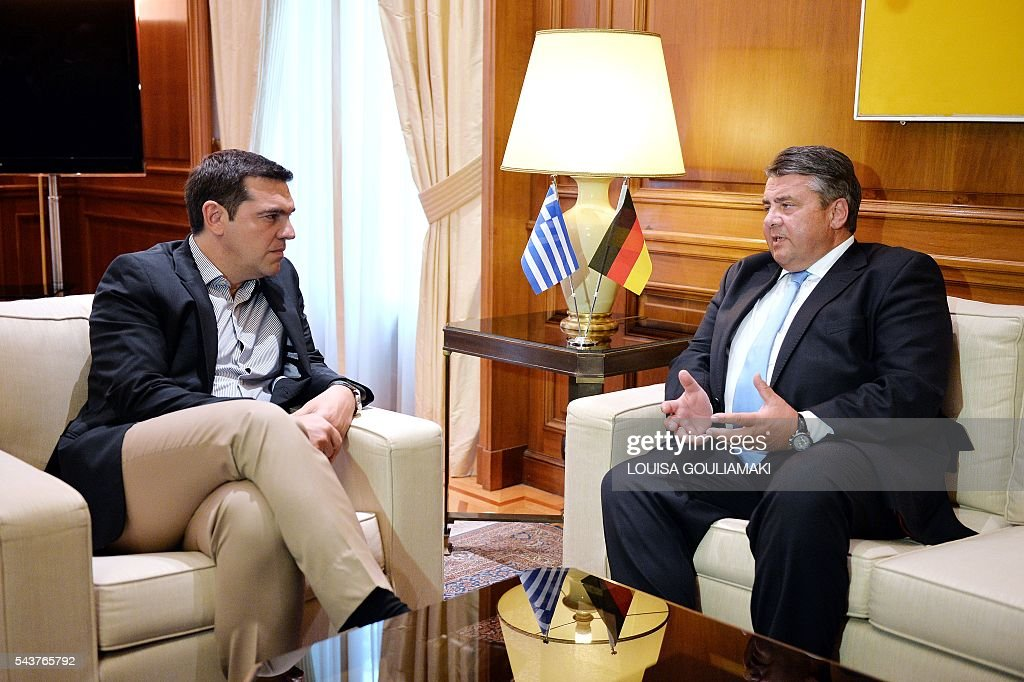 Greece's Prime Minister Alexis Tsipras (L) chats with Germany's vice chancellor and economy minister Sigmar Gabriel prior their talks in Athens on June 30, 2016. / AFP / LOUISA