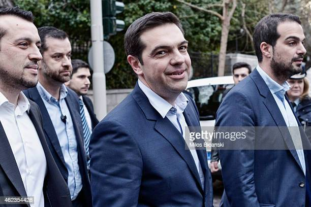 Greece's Prime Minister Alexis Tsipras is accompanied by associates as he walks out of his office on his way to the Presidential Palace to attend his...