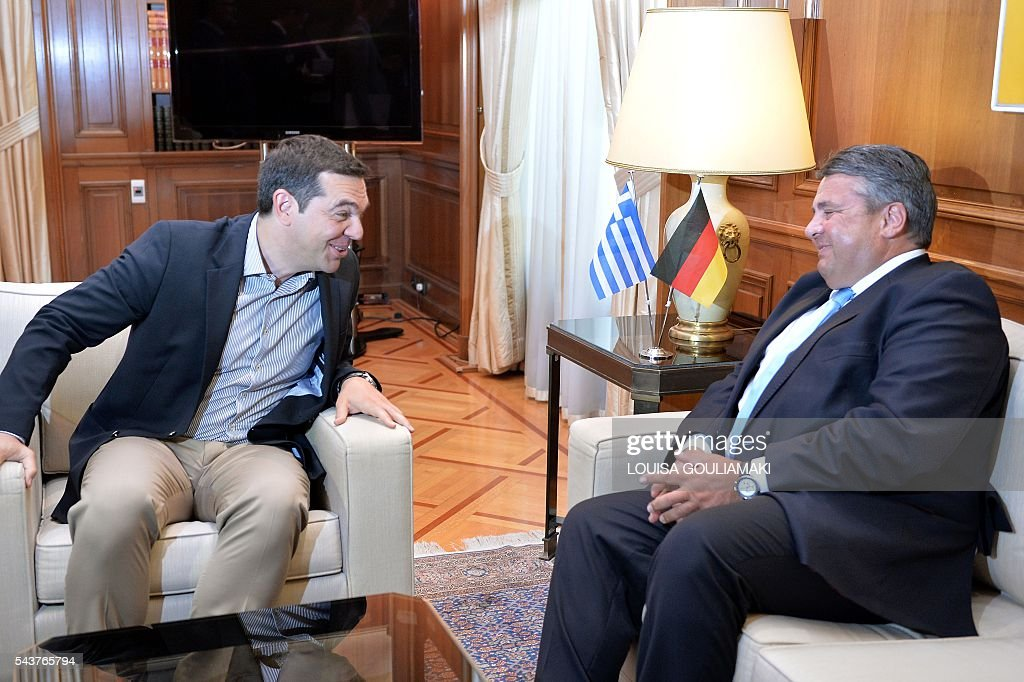 Greece's Prime Minister Alexis Tsipras (L) jokes with Germany's vice chancellor and economy minister Sigmar Gabriel prior their talks in Athens on June 30, 2016. / AFP / LOUISA
