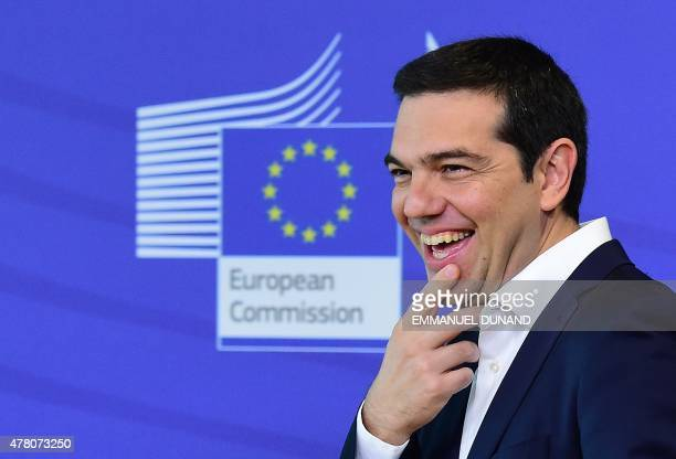 Greece's Prime Minister Alexis Tsipras laughs as he welcomed by the European Commission president ahead of an emergency summit with the leaders of...