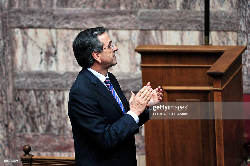 Greece's Prime minister Antonis Samaras applauds during a presentation of a draft budget to parliament outlining new austerity measures needed to unlock fresh rescue loans on October 31, 2012, in Athens. Greece revised downwards its recovery forecasts in a 2013 budget that predicted an economic contraction of 4.5 percent of output and a public deficit of 5.2 percent.