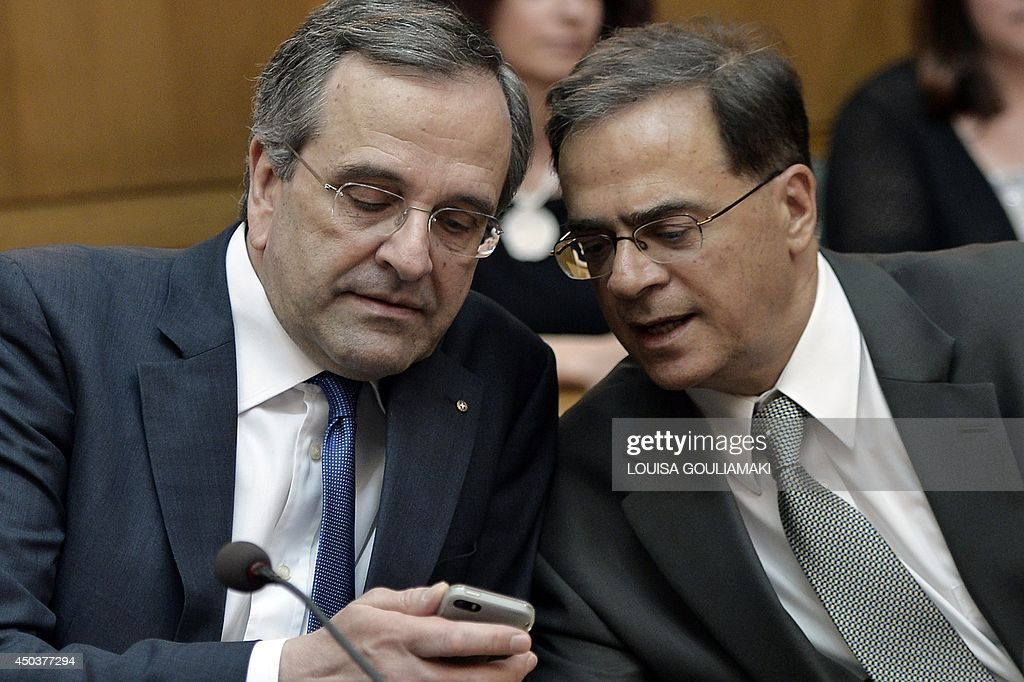 Greece's prime minister Antonis Samaras checks a mobile phone with newly appointed Finance minister Gkikas Hardouvelis (R) during a cabinet meeting at the Greek parliament in Athens on June 10, 2014. Samaras oversaw a major cabinet reshuffle on Monday in response to his government's poor showing in EU elections last month, with the crucial finance portfolio going to professor and economist Gkikas Hardouvelis .