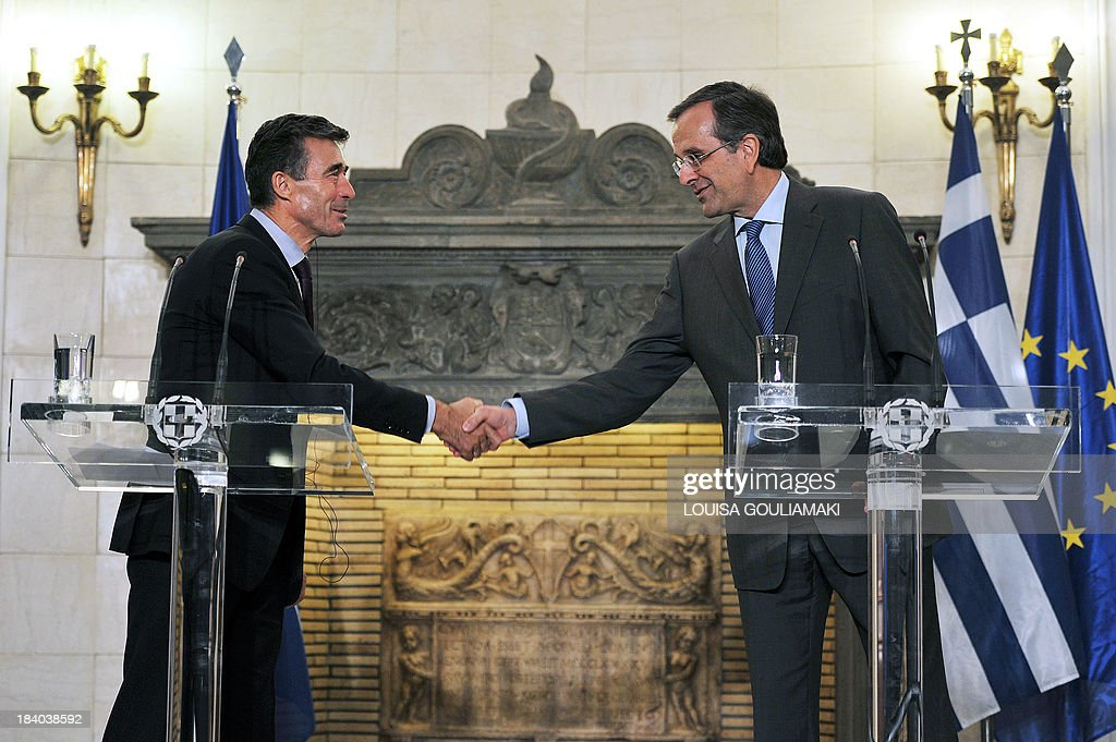 Greece's Prime minister Antonis Samaras (R) shakes hands with NATO's General Secretary Anders Fogh Rasmussen during their joint statements to the press on October 11, 2013. Rasmussen is in Greece on a two day visit.