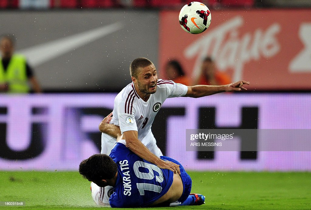 Greece's Sokratis Papastathopoulos (bottom) challenges Latvia's Maris Verpakovskis during the 2014 World Cup European zone group G qualifying football match in Athens on September 10, 2013. AFP PHOTO / ARIS MESSINIS