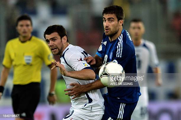 Greece's Sokratis Papastathopoulos fights for the ball with Bosnia Herzegovina's Zvjezdan Misimovic during their 2014 World Cup qualification...
