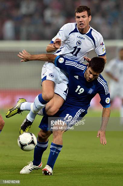 Greece's Sokratis Papastathopoulos fights for the ball with BosniaHerzegovina's Edin Dzeko during their 2014 World Cup qualifier football match in...