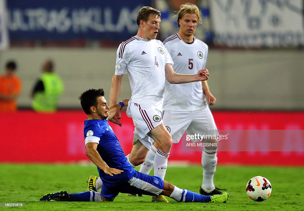 Greece's Sotiris Ninis (L) challenges Latvia's Nauris Bulvitis (C) and Juris Laizans (R) during the 2014 World Cup European zone group G qualifying football match between Greece and Latvia in Athens on September 10, 2013. AFP PHOTO / ARIS MESSINIS