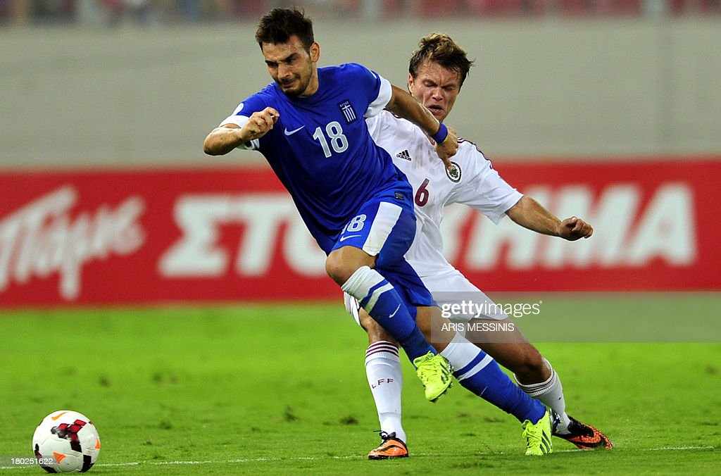 Greece's Sotiris Ninis (L) challenges Latvia's Vladislavs Gabovs during the 2014 World Cup European zone group G qualifying football match between Greece and Latvia in Athens on September 10, 2013. AFP PHOTO / ARIS MESSINIS