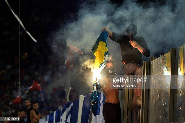 Greece's supporters burn a Bosnia Herzegovina flag during their 2014 World Cup qualification football game in Athens on October 12 2012 AFP PHOTO /...