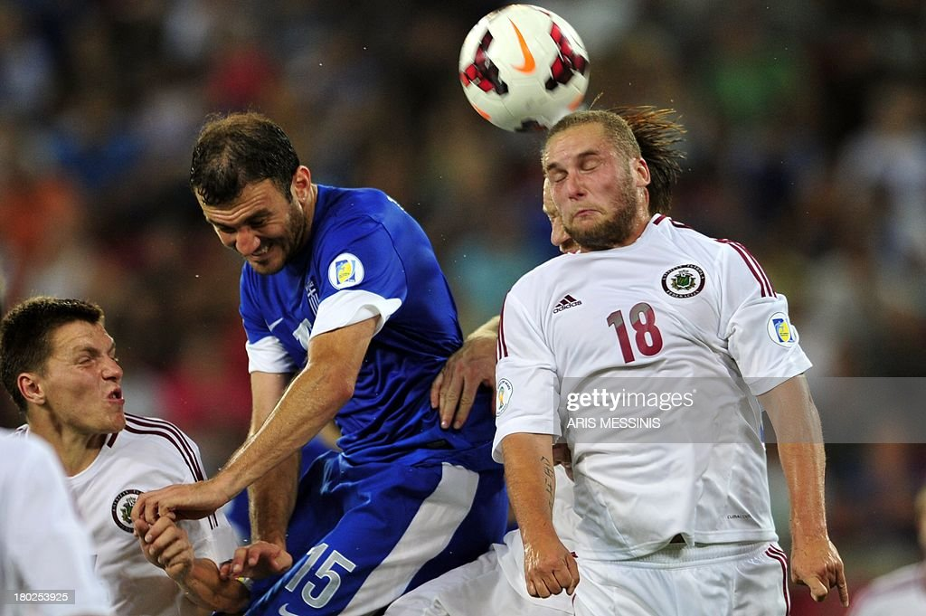 Greece's Vassilis Torosidis (C) fights for the ball with Latvia's Alans Sinelnikovs (R) on September 10, 2013 during a 2014 World Cup qualifying football match in Athens. AFP PHOTO / ARIS Messinis