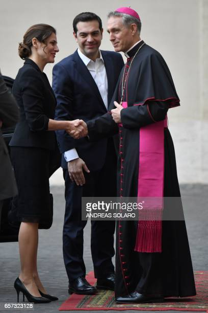 Greec's Prime Minister Alexis Tsipras and his wife Betty Batziana are welcomed by the prefect of the papal household Georg Gaenswein as she arrives...