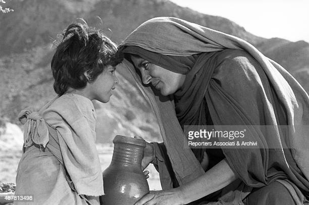 Greek actress Irene Papas in the movie Moses covered in a veil talking to a childe with a clay pot 1974