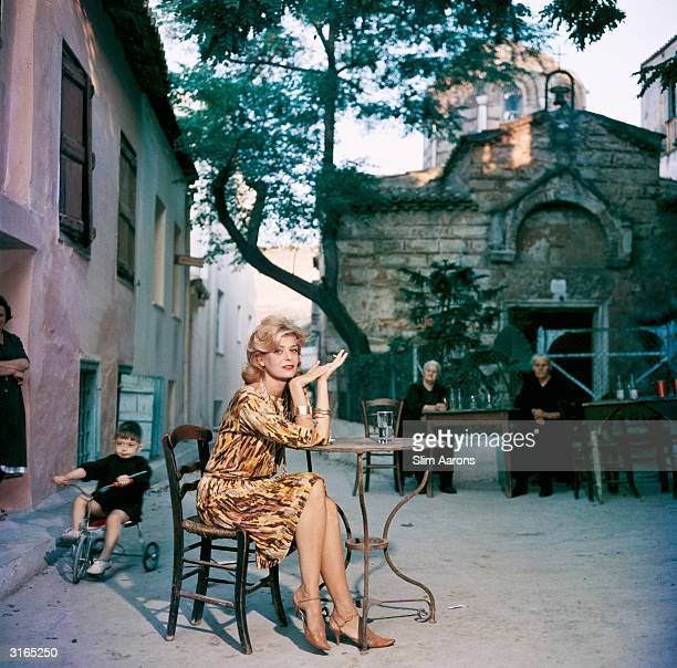 Greek actress Melina Mercouri sitting at a street cafe in Athens